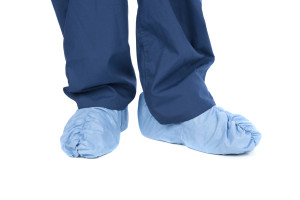 A doctor wearing protective medical scrubs and feet coverings.