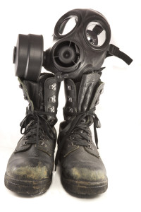 Picture of a couple of dirty old used millitary boots and a gasmask