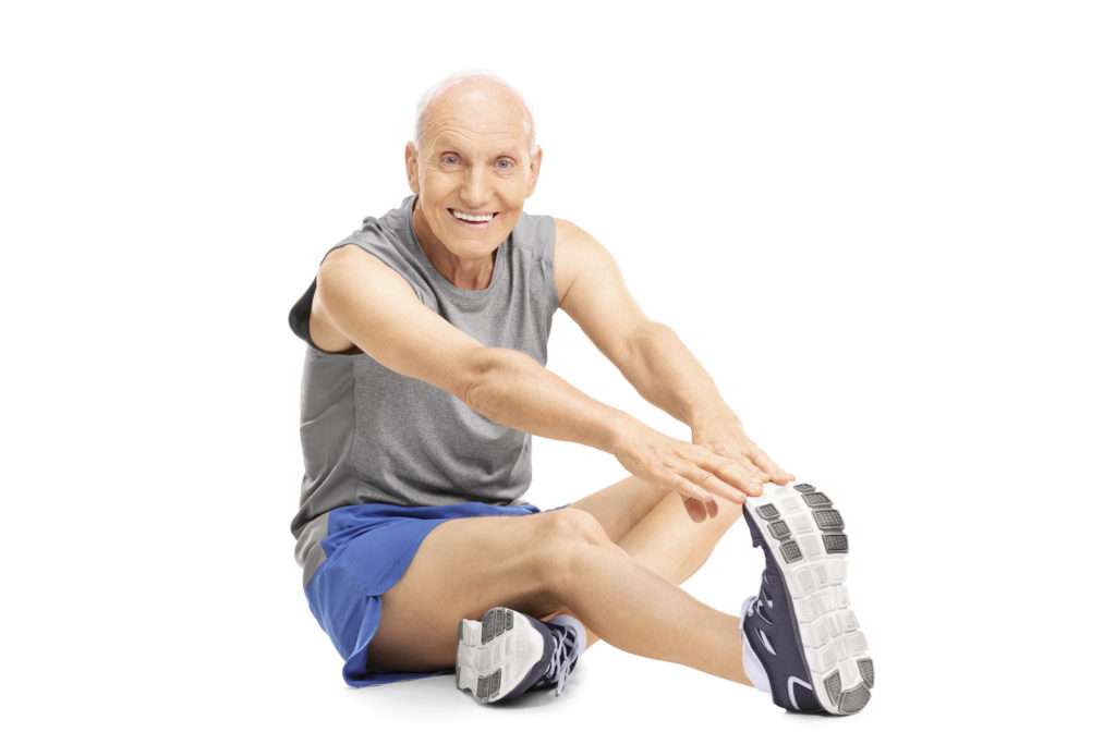 Studio shot of a senior in sportswear stretching his leg seated on the floor isolated on white background